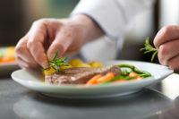 Chef decorating a dish in restaurant kitchen