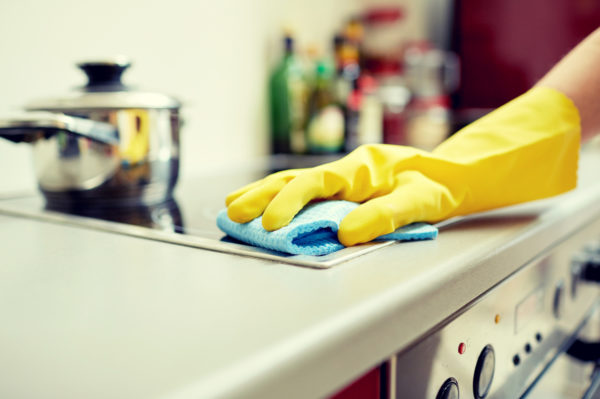 close up of woman cleaning cooker at home kitchen